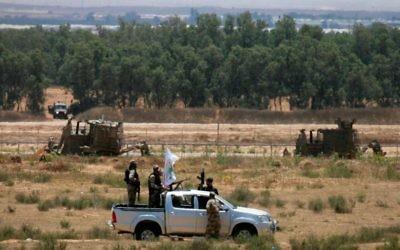 Des hommes armés des Brigades Ezzedine al-Qassam, la branche armée du Hamas, patrouillent près de la frontière israélienne de la bande de Gaza, dans la région de Rafah, le 3 juin 2015. (Crédit : Abed Rahim Khatib/Flash90)