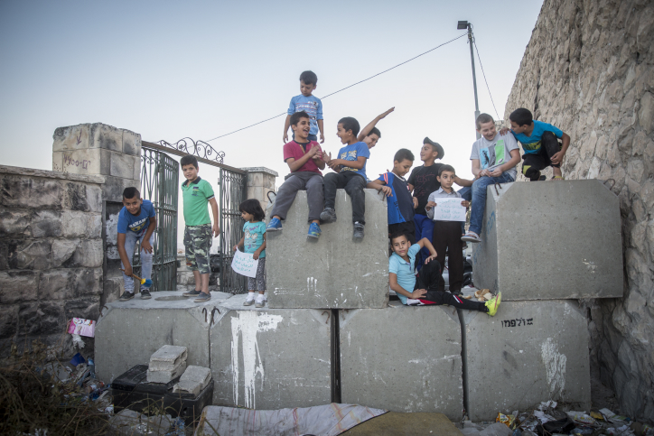Palestinian children pose on top of cement blocks placed by the Israeli army in the East Jerusalem neighborhood of Ras al Amud, on October 21, 2015. (Hadas Parush/Flash90)