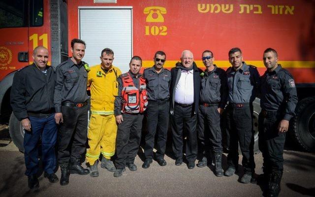Le président Reuven Rivlin (au centre, avec une écharpe) et les pompiers à Nataf, près de Jérusalem, un village qui a été touché par un important incendie en novembre 2016. (Crédit : Mark Neyman/GPO)