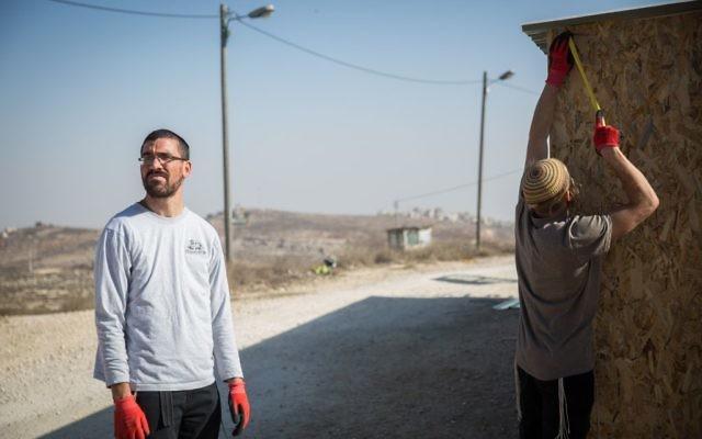 De jeunes hommes juifs construisent une structure dans l'avant-poste d'Amona, en Cisjordanie, le 28 novembre 2016. (Crédit : Hadas Parush/Flash90)