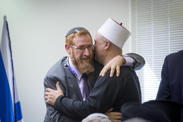 Yehuda Glick, rabbin et député du Likud, avec un dirigeant religieux druze pendant une réunion sur le projet de loi des muezzins, à la Knesset, le 5 décembre 2016. (Crédit : Miriam Alster/Flash90)