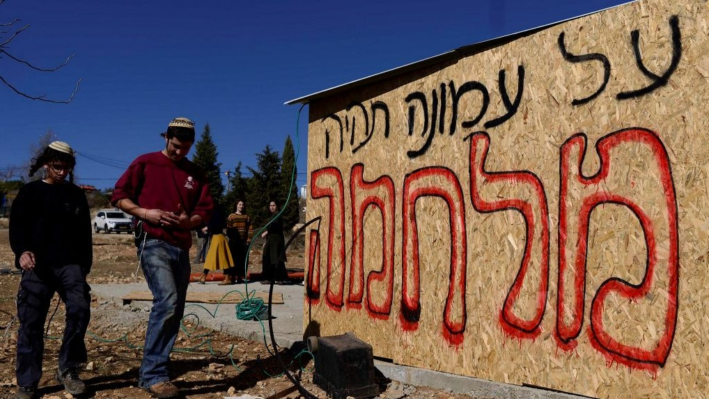 """De jeunes juifs préparent des endroits pour permettre à leurs partisans de dormir, alors qu'ils prévoient de résister à l'évacuation de l'avant-poste d'Amona, en Cisjordanie, le 9 décembre 2016. L'inscription dit : """"il y aura une guerre pour Amona."""" (Crédit : Tomer Neuberg/Flash90)"""