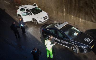 La police examine un véhicule qui s'est coincé dans un passage souterrain inondé à Haïfa, ce qui a entraîné la mort de son conducteur, le 13 décembre 2016. (Crédit : Basel Awidat/Flash90)