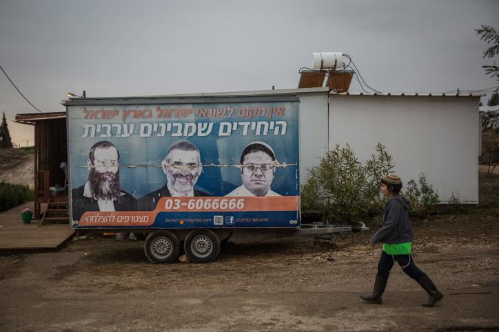 Un jeune juif passe devant une vieille publicité présentant les activistes d'extrême-droite Ben Gvir, Baruch Marzel,et Michael Ben Ari, dans l'implantation juive d'Amona, en Cisjordanie, le 16 décembre 2016. (Crédit : Hadas Parush/Flash90)