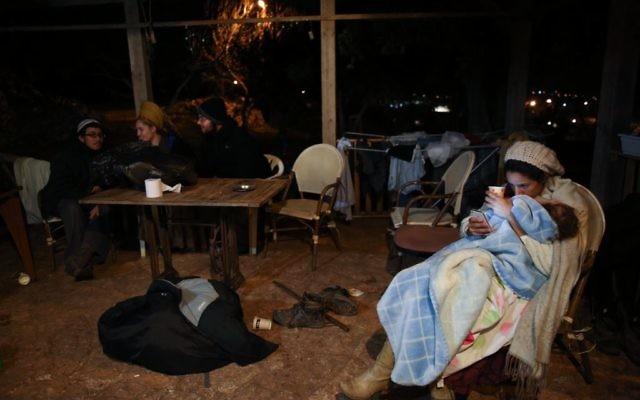 Des familles assises devant une maison de l'avant-poste d'Amona, en Cisjordanie, le 17 décembre 2016. (Crédit : Miriam Alster/Flash90)