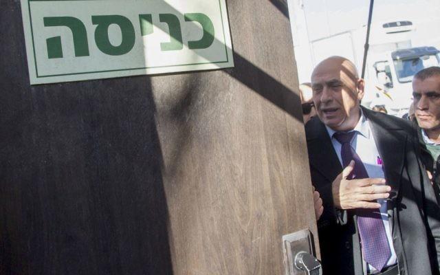 Le membre de la Knesset de la Liste (Arabe) Unie  Basel Ghattas,au centre, arrive aux bureaux de l'unité policière d'enquête Lahav 433 à Lod, le 20 décembre 2016 (Crédit : Roy Alima/Flash90)