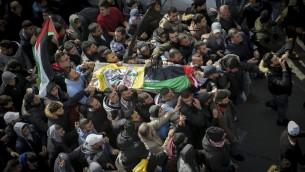 Des Palestiniens endeuillés transportent le corps d'Ahmad al-Kharoubi, 19 ans, tué par balle pendant des affrontements contre l'armée israélienne, au cours de ses funérailles à Ramallah, en Cisjordanie, le 22 décembre 2016. (Crédit : Flash90)