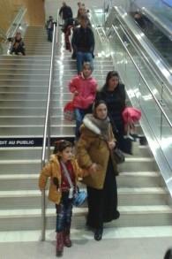 Des familles Yézidies accueillies par des bénévoles locaux à l'aéroport de Winnipeg, dans le Manitoba le 20 décembre 2016 (Crédit : Nafiya Naso)