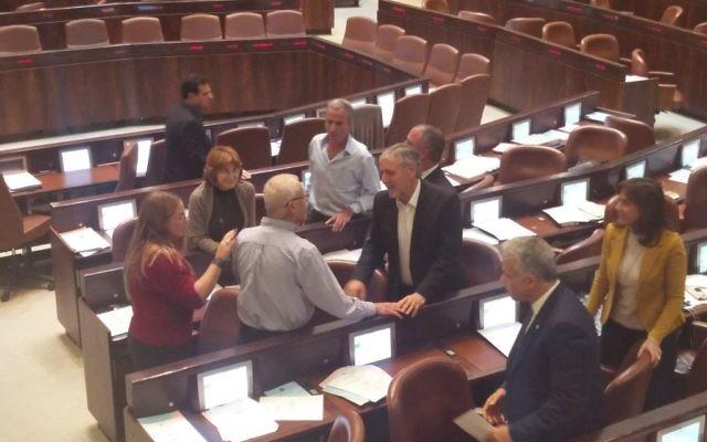 Le député du Likud Benny Begin, en chemise bleue, félicité par des députés de l'opposition à la Knesset, le 7 décembre 2016. (Crédit : Raoul Wootliff/Times of Israel)