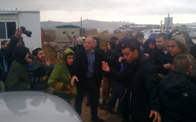 Yoav Galant, ministre du Logement, quitte Amona entouré par des manifestants qui se sont rassemblés dans l'avant-poste de Cisjordanie dans l'espoir 'empêcher son évacuation, le 18 décembre 2016. (Crédit : Judah Ari Gross/Times of Israel)