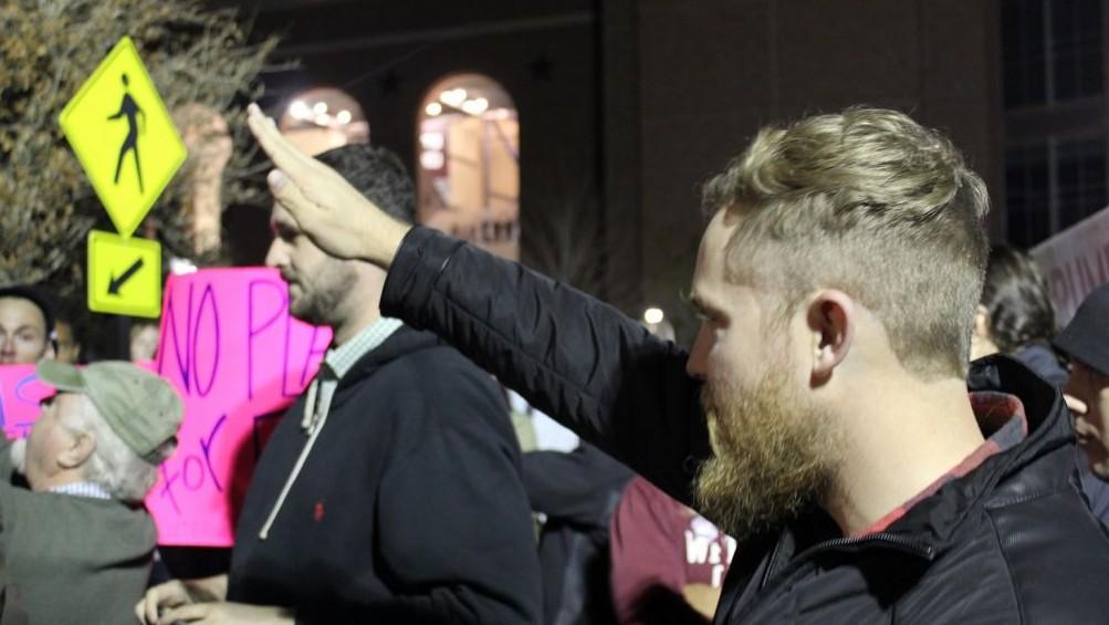 Un homme réalise un salut nazi à l'université Texas A&M, pendant que le leader de la droite alternative, Richard Spencer, prononce un discours, le 6 décembre 2016. (Crédit : Ricky Ben-David/Times of Israel)