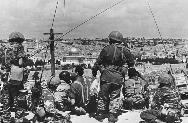 Mordechai 'Motta' Gur (assis, avec les cheveux noirs et frisés) et ses troupes surveillent la vieille ville avant de lancer une attaque en mai 1967 (Crédit : t: Wikimedia Commons CC BY-SA/Mazel123)