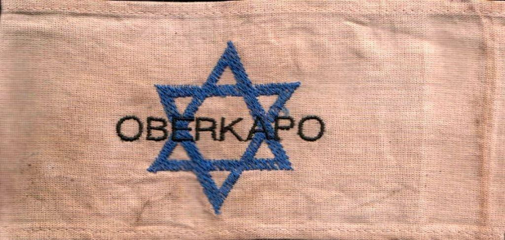 Un brassard de chef 'Kapo' datant de la période de l'Holocauste, porté par un détenu juif chargé des fonctions administratives. (Domaine public)