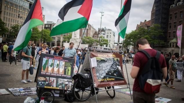 """Des touristes israéliens devant un stand du BDS avec des photos et des drapeaux palestiniens, appelant à la """"Palestine libre"""", à  sur la place de Dam, au centre d'Amsterdam, en Hollande, le 24 juin 2016. (Crédit : Hadas Parush/Flash90)"""
