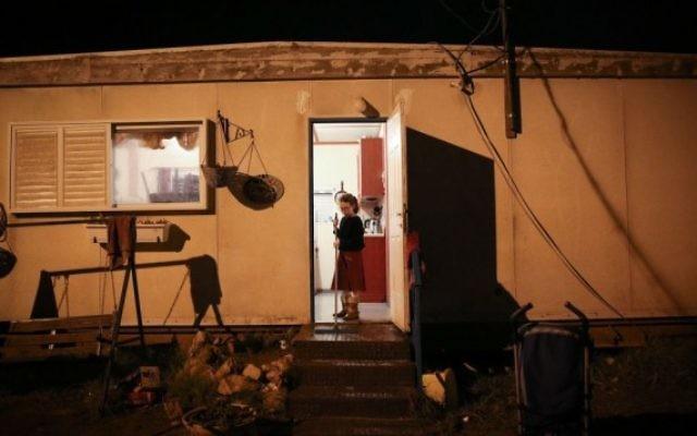 Une jeune israélienne à l'entrée de son habitation à l'avant-poste d'Amona en Cisjordanie, le 17 décembre   2016. (Crédit : Miriam Alster/Flash90)