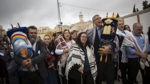 Des rabbins conservateurs réformés américains et des membres des Femmes du Mur brandissent des rouleaux de Torah durant une manifestation contre l'absence de construction d'un nouvel espace de prière, au mur Occidental, dans la Vieille Ville de Jérusalem, le 2 novembre 2016. (Crédit : Hadas Parush/Flash90)