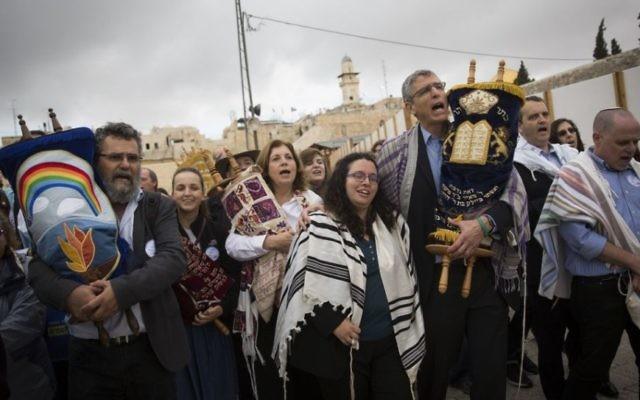 Des rabbins conservative et réformés américains et des membres des Femmes du Mur brandissent des rouleaux de la Torah durant une manifestation contre l'absence de construction d'un nouvel espace de prière, au mur Occidental, dans la Vieille Ville de Jérusalem, le 2 novembre 2016. (Crédit : Hadas Parush/Flash90)