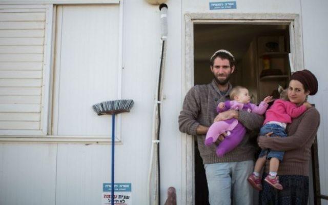Neria, à gauche, Tova, à droite, et leurs deux enfants devant l'entrée de leur habitation dans l'avant-poste d'Amona, en Cisjordanie, le 16 décembre 2016. (Crédit : Hadas Parush/Flash90)