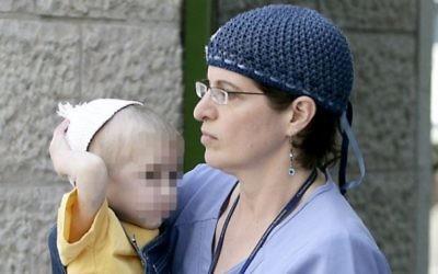 Une infirmière porte dans ses bras la petite victime présumée de sa mère, à Jérusalem, le 26 juillet 2009. (Crédit : Abir Sultan/Flash90)