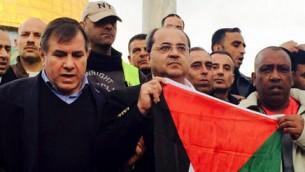 Ahmad Tibi brandit un drapeau palestinien sur le sommet du mont du Temple, le 3 janvier 2015 (Crédit : Deuxième chaîne /Tamar Abidat)