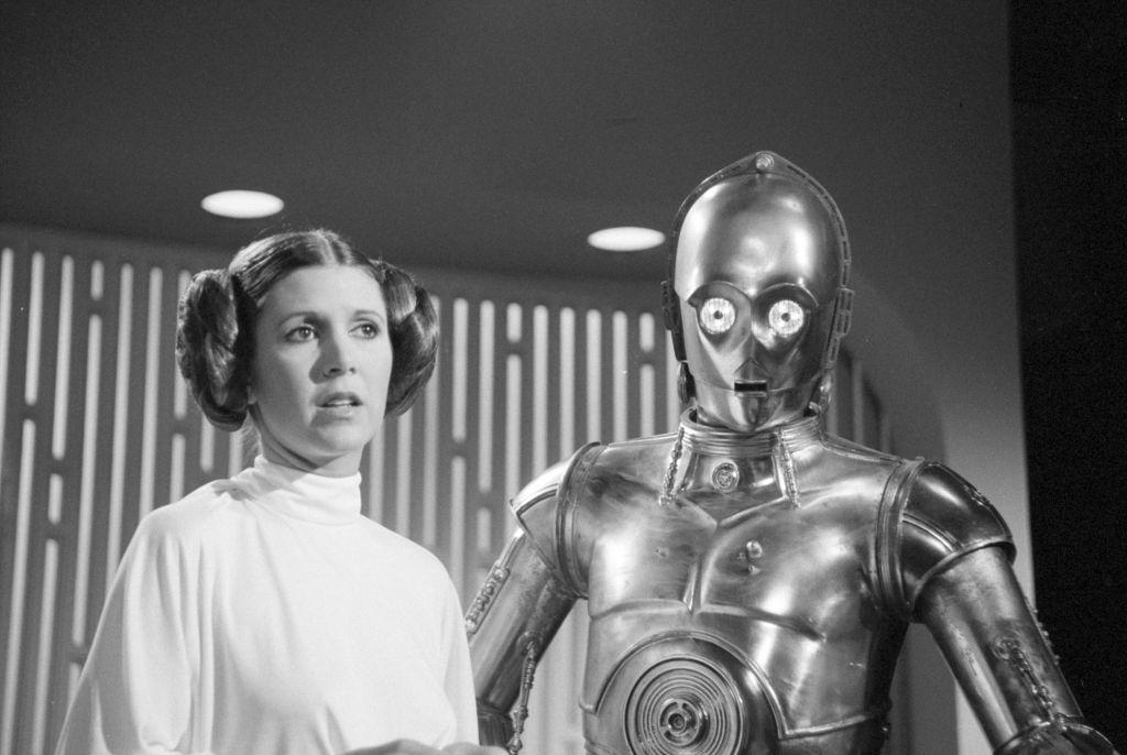 """Carrie Fisher dans son rôle de Princesse Leia de """"Star Wars"""", aux côtés de C-3PO, le 23 août 1978. (Crédit : CBS via Getty Images)"""
