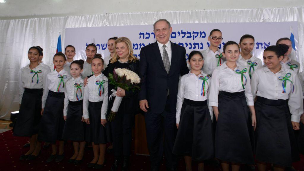 Le Premier ministre Benjamin Netanyahu et sa femme Sara avec la chorale d'enfants à Or Avner, complexe scolaire juif à Baku, en Azerbaïdjan, le 13 décembre 2016. (Crédit : Haim Zach/GPO)