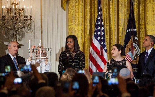 Mika Almog, petite-fille de l'ancien président israélien Shimon Peres, allume la hanoukkiah pendant que madame le rabbin Rachel Isaacs récite les bénédictions dans l'East Room de la Maison Blanche le 14 décembre 2016 à Washington, DC, avec Chemi Peres, le président Barack Obama et la Première dame Michelle Obama. (Crédit : AFP/ ZACH GIBSON)