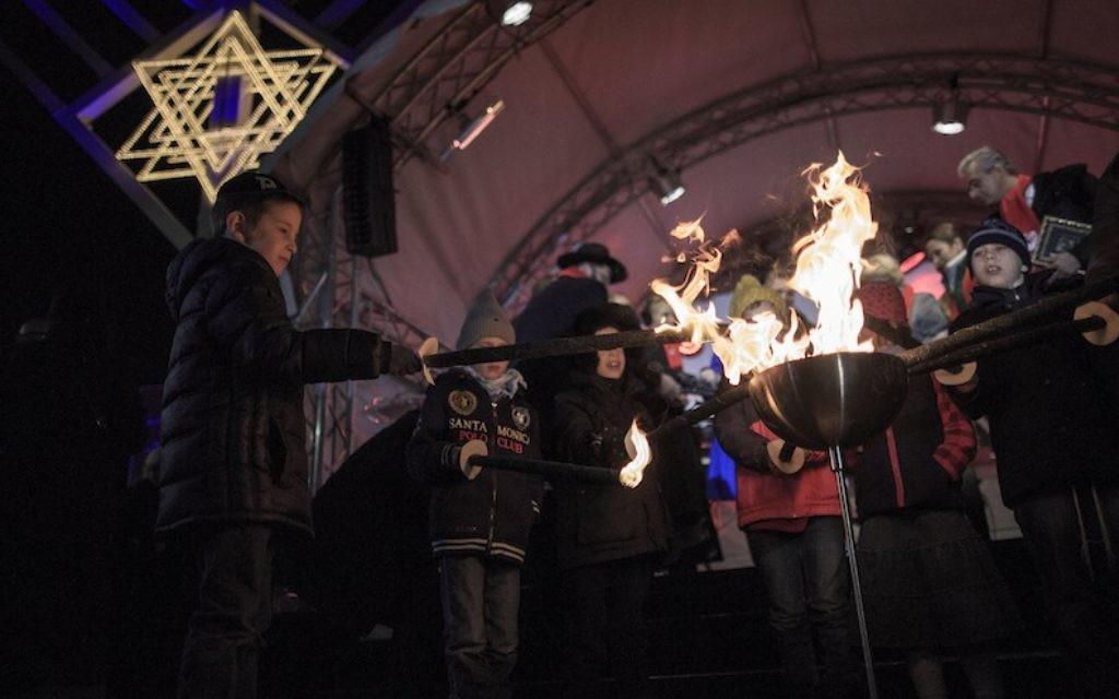 Des enfants éclairent des torches lors d'une cérémonie d'allumage d'une menorah d'Hanoukka à proximité de la porte de  Brandenburgle 6 décembre 2015 à Berlin, en Allemagne. (Crédit :  Carsten Koall/Getty Images)