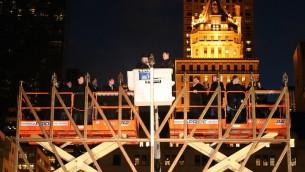 La plus grande Hannoukiah du monde sur la Cinquième Avenue près de Central Park allumée en 2013 par le maire de la ville de New York, Michael R. Bloomberg, avec le rabbin Shmuel M. Butman, le directeur de l'organisation jeunesse Loubavitch (Crédit : PRNewsFoto / Agence d'information juive)