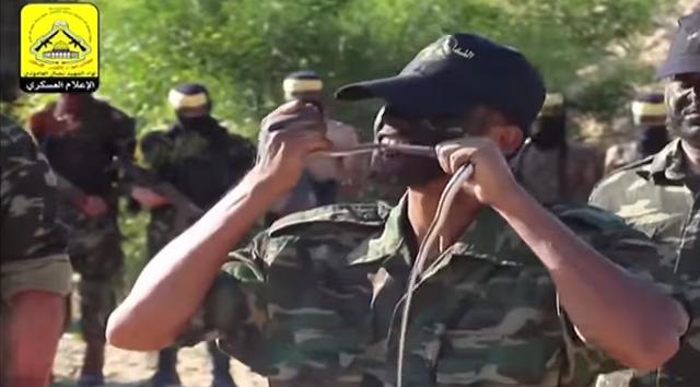 Un combattant du Fatah mord et mâche un serpent dans une vidéo pour promouvoir le terrorisme postée sur la page Facebook du groupe en novembre 2015. (Crédit : capture d'écran YouTube)