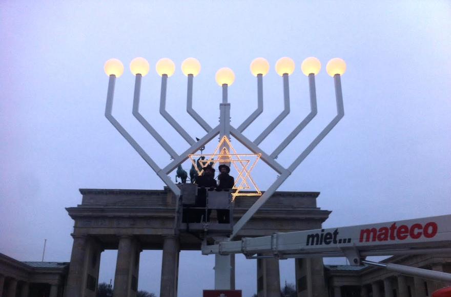 Le rabbin Yehudah Teichtal, à gauche, et un collègue mettent à l'épreuve une menorah de Hanoukka à la porte de Brandenburg à Berlin, le 22 décembre 2016 (Autorisation de  Teichtal/via JTA)