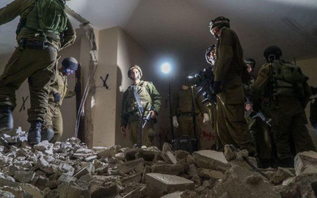 Des soldats israéliens détruisent la maison de Mesbah Abu Sabih, un Palestinien qui a tué deux Israéliens pendant une attaque à main armée à Jérusalem en octobre 2016, dans le quartier Kafr Aqab de Jérusalem Est, le 22 décembre 2016. (Crédit : unité des portes-paroles de l'armée israélienne)