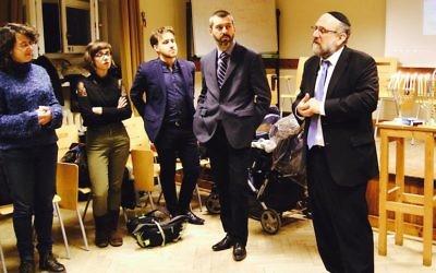 Le Rabbin Michael Schudrich, à droite, s'adresse aux étudiants lors de l'événement organisé pour Hanoukka au département judaïque de l'université de Varsovie, le 20 décembre 2016 (Autorisation  Schudrich)