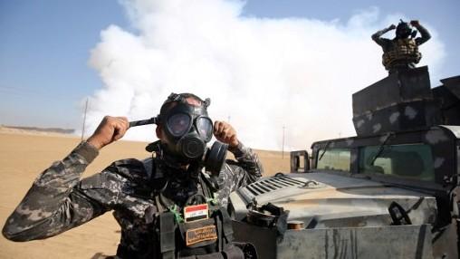 Des forces irakiennes avec des masques à gaz pour se protéger de la fumée après la mise en feu par l'Etat islamique d'une usine de sulfure, près de la base de Qayyarah, à 30 km au sud de Mossoul, le 22 octobre 2016. (Crédit : Ahmad Al-Rubaye/AFP)