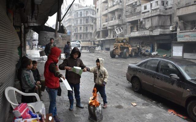 Des enfants syriens rassemblés autour d'un feu dans les rues d'Alep, pendant l'offensive gouvernementale pour reprendre la ville, le 27 décembre 2016. (Crédit : George Ourfalian/AFP)