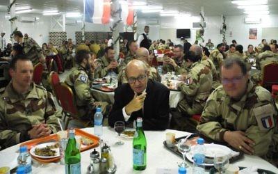Le (vrai) ministre français de la Défense, Jean-Yves Le Drian, au centre, entourés des soldats de l'armée de l'air française sur une base militaire de Jordanie, le 31 décembre 2016. (Crédit : Valérie Leroux/AFP)