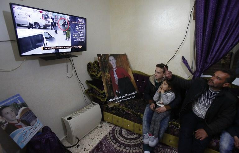 Yousri al-Sharif, le père d'Abdel Fattah al-Sharif, regarde à la télévision le verdict d'Elor Azaria, le soldat israélien qui a tué son fils, dans sa maison de Hébron, en Cisjordanie, le 4 janvier 2017. (Crédit : Hazem Bader/AFP)