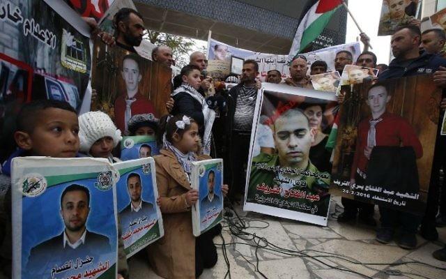 Des Palestiniens rassemblées dans les rues de Hébron, en Cisjordanie, pendant le verdict du soldat israélien Elor Azaria (portrait, au centre) qui a tué Abdel Fattah al-Sharif (portrait, à gauche), le 4 janvier 2017. (Crédit : Hazem Bader/AFP)