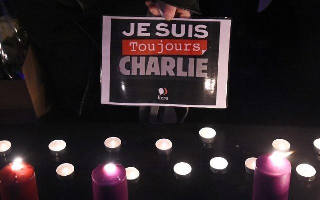 """Une personne tient une pancarte """"Je suis toujours Charlie"""" lors d'un rassemblement commémorant le deuxième anniversaire de l'attentat meurtrier contre l'hebdomadaire satirique """"Charlie Hebdo"""", le 7 janvier 2017, place de la République à Paris. (AFP PHOTO / BERTRAND GUAY)"""