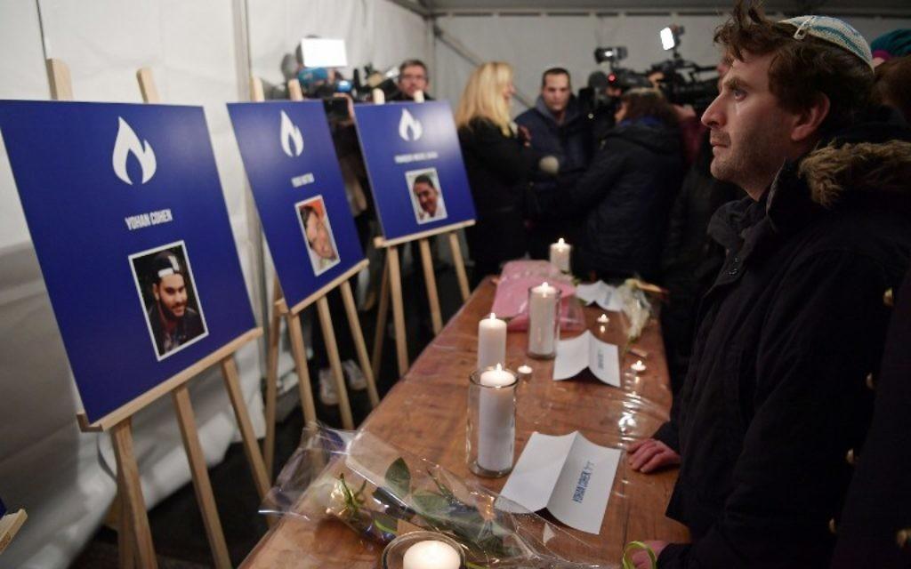 Un homme se tient debout devant des bougies et des photos de Philippe Braham, Yohan Cohen, Yoav Hattab et François Michel Saada tués dans l'attaque mortelle contre le supermarché Hyper Cacher en 2015, lors d'une cérémonie marquant le deuxième anniversaire de l'attaque contre le magasin, à Paris le 9 janvier 2017. (Crédit : AFP PHOTO / CHRISTOPHE ARCHAMBAULT)