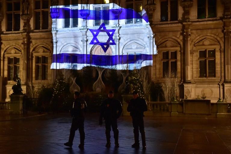 Des CRS en patrouille devant l'Hôtel de Ville de Paris, illuminé du drapeau israélien après un attentat au camion bélier qui a tué 4 soldats à Jérusalem, le 10 janvier 2017. (Crédit : Christophe Archambault/AFP)