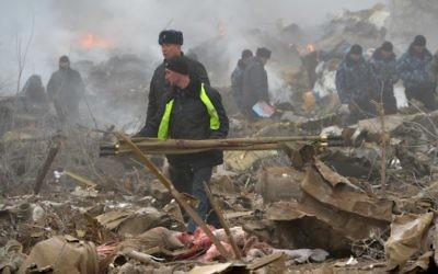 Les personnels de secours sur le site où un avion s'est écrasé dans le village de Datcha-Souou, près de Bishkek, au Kirghizstan, le 16 janvier 2017. (Crédit : Vyacheslav Oseledko/AFP)