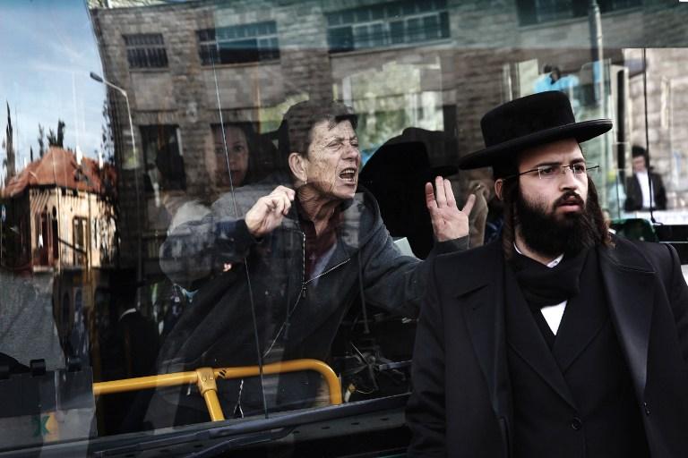 Une femme furieuse dans un bus bloqué par des ultra-orthodoxes manifestant contre l'emprisonnement d'une jeune ultra-orthodoxe n'ayant pas demandé d'exemption de service militaire, dans le quartier Mea Shearim de Jérusalem, le 17 janvier 2017. (Crédit : Menahem Kahana/AFP)