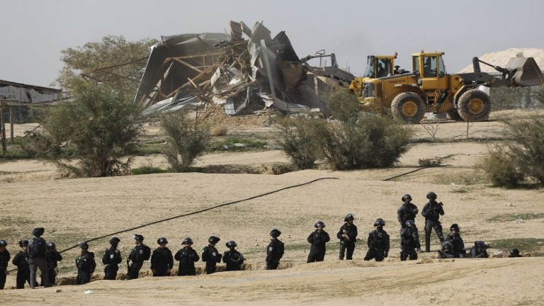 Des policiers israéliens déployés pendant des démolitions dans le village bédouin non reconnu d'Umm al-Hiran, dans le Néguev, le 18 janvier 2017. (Crédit : Menahem Kahana/AFP)