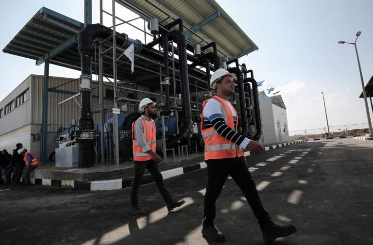 Des travailleurs palestiniens de l'usine de désalinisation de l'eau pendant l'inauguration de sa première phase à Deir al-Balah, dans le centre de la bande de Gaza, le 19 janvier 2017. (Crédit : Saïd Khatib/AFP)