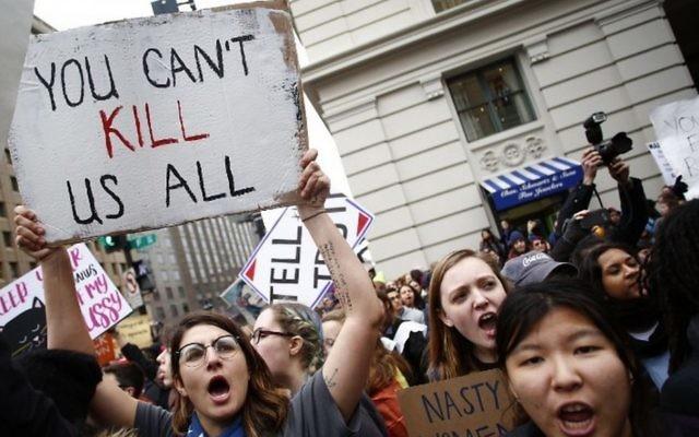 Des manifestantes entourent un char de la parade en provoquant des partisans de Trump lors de la Marche des femmes du 21 janvier 2017 à Washington (Crédit : Joshua Lott/AFP)