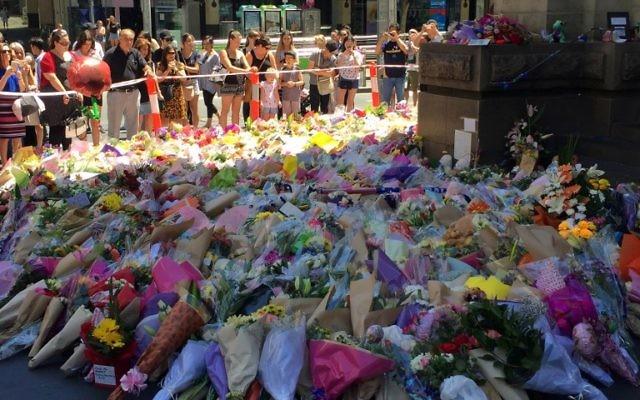 Des centaines de fleurs déposées sur les lieux d'un carnage qui a tué au moins 5 personnes, dont un bébé de 3 mois et une fillette juive de 10 ans, à Melbourne, en Australie, le 22 janvier 2017. (Crédit : Saeed Khan/AFP)