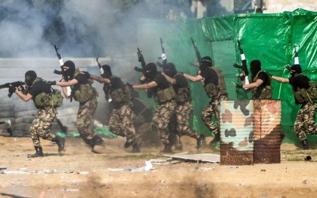 Des membres des forces de sécurité palestiniennes du Hamas présentent un faux raid contre un poste de l'armée israélienne pendant la cérémonie de fin d'un programme de formation militaire du Hamas, à Gaza Ville, le 22 janvier 2017. (Crédit : Mahmud Hams/AFP)