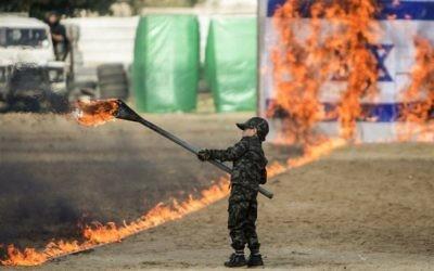 Un petit garçon palestinien enflamme un drapeau israélien pendant la cérémonie de fin d'un programme de formation militaire du Hamas, à Gaza Ville, le 22 janvier 2017. (Crédit : Mahmud Hams/AFP)