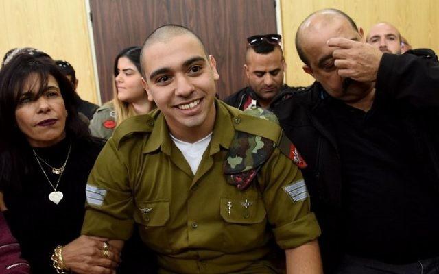 Elor Azaria, jugé coupable d'homicide après avoir tué un terroriste palestinien neutralisé, avec ses parents devant le tribunal militaire de Tel Aviv, le 24 janvier 2017. (Crédit : Debbie Hill/AFP)